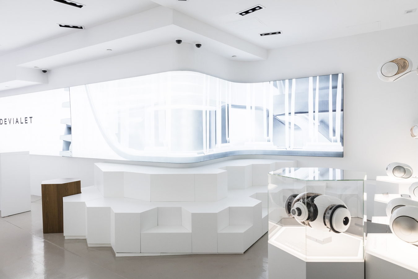 A view of the store's white interior space with Phantom speakers on display and a seating area of angular blocks.