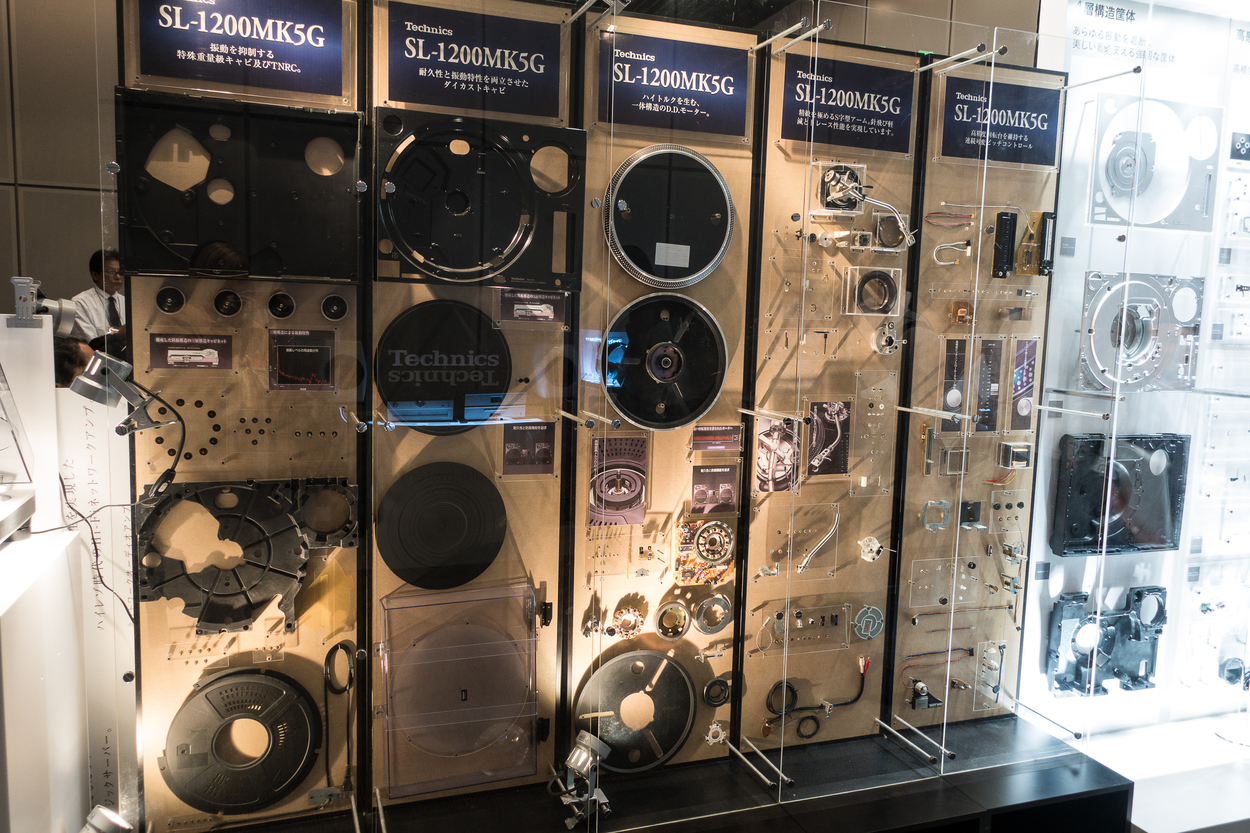 A clear, vertical display case showing all the parts of a Technics SL-1200MK5G turntable disassembled.